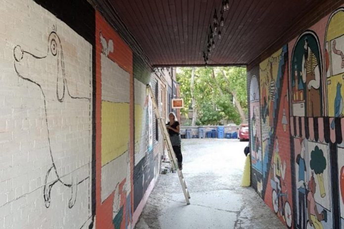 Kathryn Durst working on her latest mural in the Commerce Building alleyway in downtown Peterborough. (Photo: Dave Fry)
