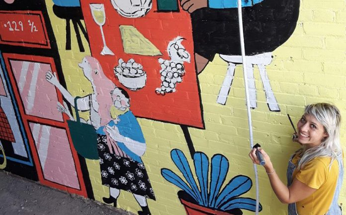 Peterborough illustrator Kathryn Durst at work on her mural in the alleyway of the Commerce Building in downtown Peterborough. The mural, commissioned by the First Friday Peterborough volunteer committee and Commerce Building owner Ashburnham Realty, will be celebrated from 6 to 10 p.m. on Friday, September 4, 2020. (Photo: First Friday Peterborough / Facebook)