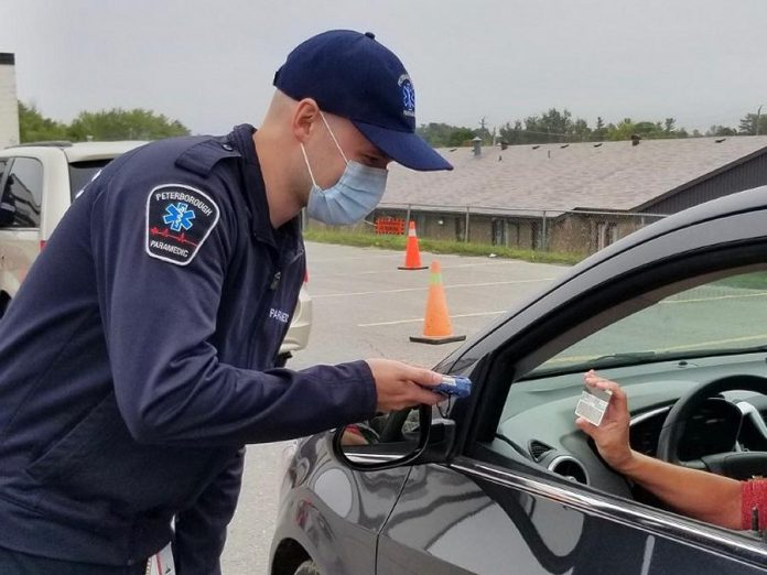 When people arrive for a test at the drive-through COVID-19 testing clinic in Peterborough, staff use a handheld device to scan their health card and driver's licence to digitally capture patient information for the laboratory requisition. This ensures more complete and legible information accompanies the lab requisition for the test. (Photo courtesy of PRHC)
