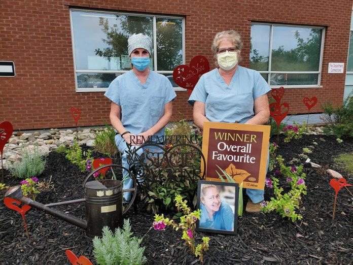 """Theresa Connell and Marlene Dawson of Ross Memorial Hospital in Lindsay, two colleagues of late emergency department nurse Stacie Vokins, stand in the garden they dedicated to the memory of Vokins (shown in the picture frame), a 20-year employee of the hospital who passed away in November 2019. The garden, which includes heart sculptures by local artist Christina Handley, won the hospital's annual """"Garden Cup"""". (Photo courtesy of Ross Memorial Hospital)"""