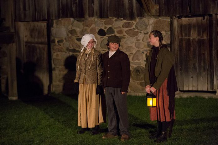 """Set on a dark fall night in 1835, 4th Line Theatre's """"Bedtime Stories and Other Horrifying Tales"""" follows 10-year-old Samuel Deyell (Lev Khaimovich, middle) as he goes into the darkest night in search of his missing mother. Samuel is joined on his quest by his two best friends (Skyleigh Hurd and Rylee Dixon) and, in the shadows, the children encounter the darkest secrets and most horrifying facets of Millbrook and Cavan. (Photo: Wayne Eardley / Brookside Studio)"""