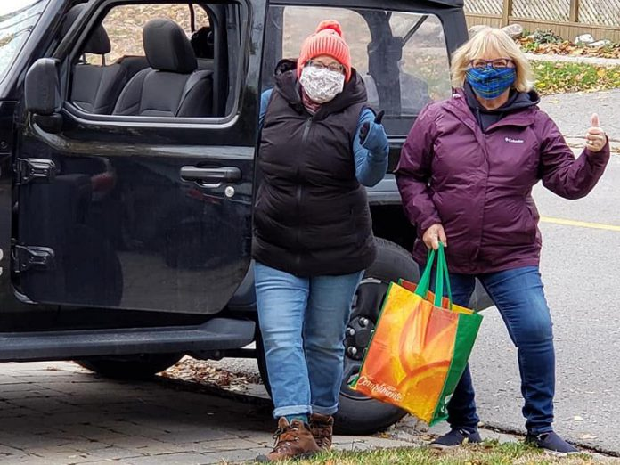 """Volunteers Susan Porter Dunkley and Anne Arnold picking up a donation in Peterborough's East City for Kawartha Food Share during the """"Spare A Square #2"""" city-wide porch food drive on October 24, 2020. (Photo: Jeannine Taylor / kawarthaNOW.com)"""