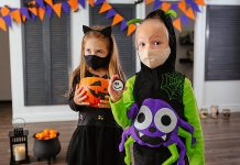 Two children wearing COVID-19 face coverings and Halloween costumes. (Stock photo)