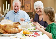 A young girl celebrating Thanksgiving with her grandparents. (Stock photo)