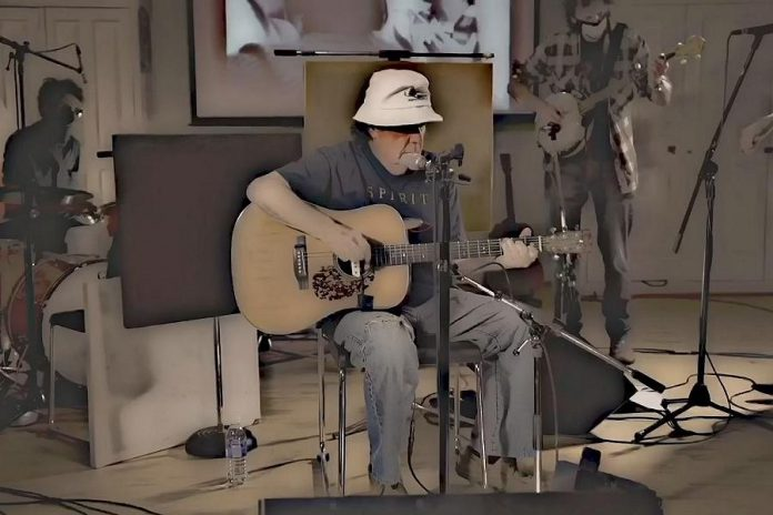 """Omemee's Bob Young performing his song """"Hey America"""" along with Peterborough musicians Ryan Weber of The Weber Brothers and Melissa Payne and Travis Good and Mike Belitsky of Toronto band The Sadies. Bob's younger brother, the legendary Neil Young, also performs in the video. (Screenshot)"""