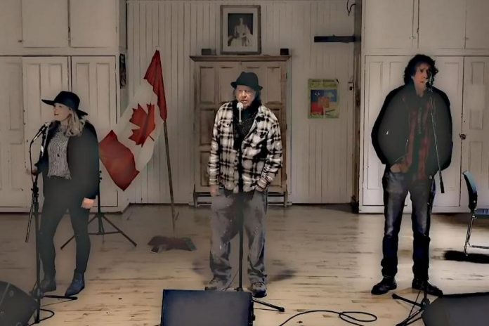 """Melissa Payne, Neil Young, and Travis Good singing harmony vocals to Bob Young's song """"Hey America"""". Due to the pandemic, the three musicians were filmed separately using the same background, and the shots were assembled in post-production to make it appear they were singing together. (Screenshot)"""