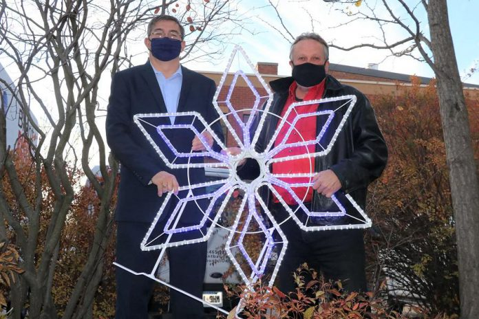 Peterborough-Kawartha MPP Dave Smith and Peterborough DBIA executive director Terry Guiel with one of the new new decorative holiday lights to be installed in downtown Peterborough. (Supplied photo)