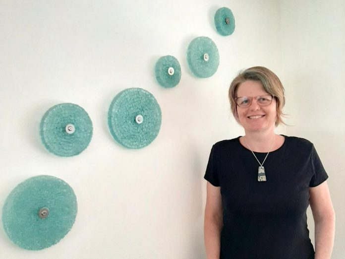 Peterborough-area artist Christy Haldane is renowned for her work in repurposed glass, which she combines with other materials such as stone, concrete, and steel. Now she is creating wearable and functional art using glass and stone, such as the hanging pendant she's wearing in this photo, available online from her website. (Photo: Miller Dodgson)