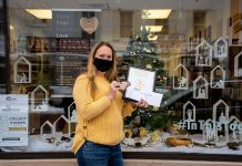 Jenni Johnston, executive director of the Art School of Peterborough at 174A Charlotte Street in downtown Peterborough, with the first place prize in the Peterborough Downtown Business Improvement Area (DBIA)'s annual holiday window contest. (Photo courtesy of Peterborough DBIA)