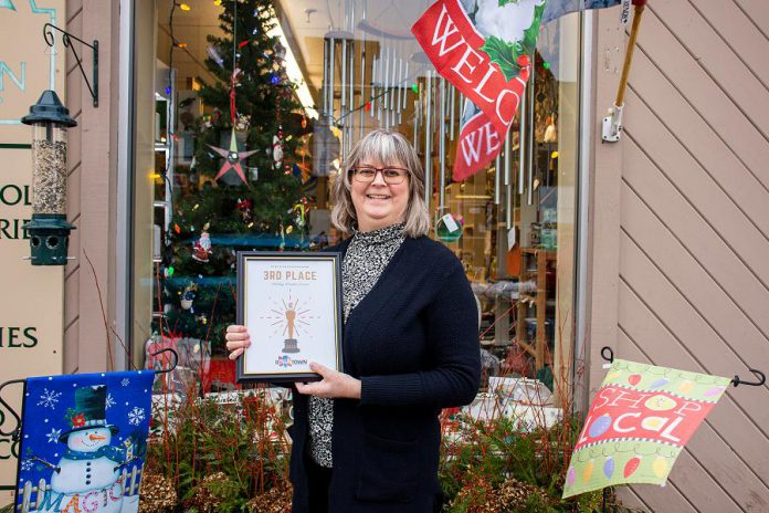 Brenda Ibey, owner of The Avant-Garden Shop at 165 Sherbrooke Street in downtown Peterborough, with the third place prize in the Peterborough Downtown Business Improvement Area (DBIA)'s annual holiday window contest. (Photo courtesy of Peterborough DBIA)