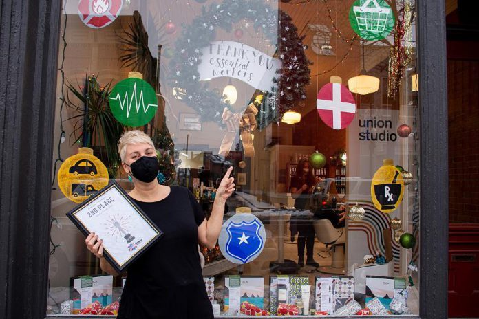 Sparo Lindsay, owner of Union Studio at 391 Water Street in downtown Peterborough, with the second place prize in the Peterborough Downtown Business Improvement Area (DBIA)'s annual holiday window contest. (Photo courtesy of Peterborough DBIA)