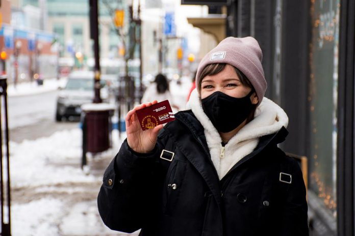 Shopper Deanna Henry displays a Downtown Dollars Gift Card now available for shopping in-store and on-line at participating businesses in downtown Peterborough. The card is available in $25, $50, $100, and $200 denominations. (Photo courtesy of Peterborough DBIA)