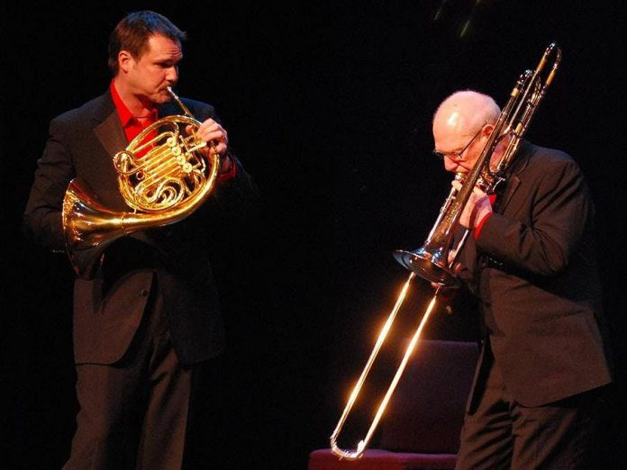 """Well before he became PSO music director, Michael Newnham had private lessons on trombone with Gene Watts (right), founder of Canadian Brass, pictured here with Canadian Brass member Jeff Nelsen on French horn performing """"Swing that Music"""" by Louis Armstrong at the Buskirk-Chumley Theater in Bloomington, Indiana in 2010. (Photo:  Allison Tyra)"""