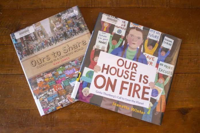"""Librarians at the Peterborough Public Library recommend these two children's titles: """"Ours to Share"""" also contains a list of several useful resources, and """"Our House is on Fire"""" is a powerful reminder that one person can make a difference. (Photo: Leif Einarson)"""