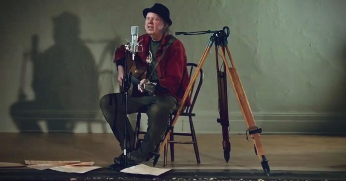 Neil Young performing 'Comes a Time' at an empty Coronation Hall in Omemee. He is making the film of his 2017 'Hometown' concert in Omemee, directed by his wife Daryl Hannah, available for free on his website during the month of December. (Screenshot)