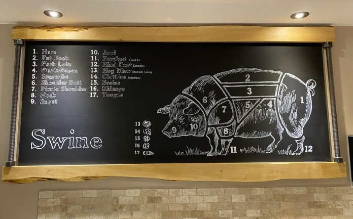 A chalkboard at Primal Cuts showing all the cuts of meat and organ meats from swine. As a nose-to-tail butcher, owner George Madill tries to use all the meat from an animal, including the bones to make broths and stocks. (Photo courtesy of Primal Cuts)