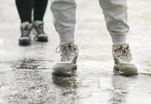 Two pedestrians walking on an icy surface. (Stock photo)