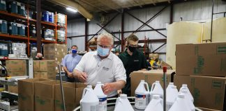 Premier Doug Ford packing bottles of disinfectant into boxes during a tour of Charlotte Products in Peterborough on July 30, 2020. Charlotte Products has ramped up production of its cleaning products during the pandemic and is facing a shortage of bottles for its products. Along with a $1 million provincial investment, Peterborough's Merit Precision is investing $1.3 million for an expansion that will allow it to supply bottles to Charlotte Products. (Photo: Government of Ontario)