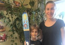 """Carlotta James of Peterborough Pollinators with her 7-year-old son Salvador Haines, who painted this canoe paddle for the Painted Paddle art exhibit, which features 20 canoe paddles painted by volunteer artists on display at various locations in downtown Peterborough throughout February. Salvador says his paddle art, called The Elements, """"represents the balance in nature with flowers blooming during the day and its roots growing by night, surrounded by the four elements: light blue for air, dark blue for water, red for fire and green for earth. Also, there's a secret word painted in the roots, can you find it?"""". (Photo: Peterborough Pollinators / Facebook)"""