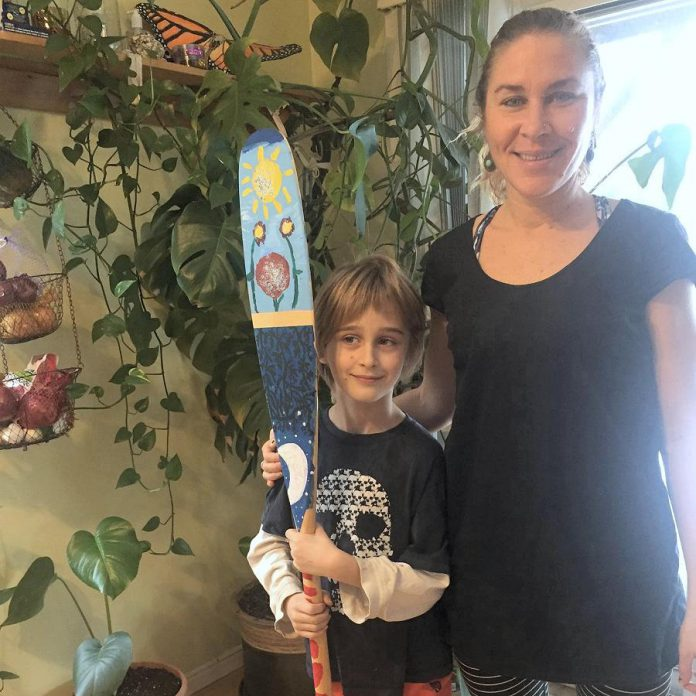 "Carlotta James of Peterborough Pollinators with her 7-year-old son Salvador Haines, who painted this canoe paddle for the Painted Paddle art exhibit, which features 20 canoe paddles painted by volunteer artists on display at various locations in downtown Peterborough throughout February. Salvador says his paddle art, called The Elements, ""represents the balance in nature with flowers blooming during the day and its roots growing by night, surrounded by the four elements: light blue for air, dark blue for water, red for fire and green for earth. Also, there's a secret word painted in the roots, can you find it?"". (Photo: Peterborough Pollinators / Facebook)"