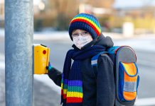 A child going to school while wearing a mask at a crosswalk. (Stock photo)