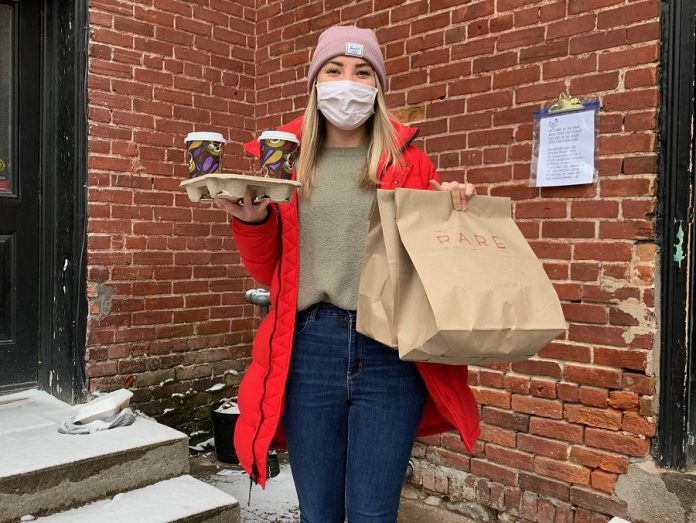 Rare employee Christina picking up food at Rare's back door. Throughout the lockdown, all Rare employees eat for free.  (Photo courtesy of Rare)