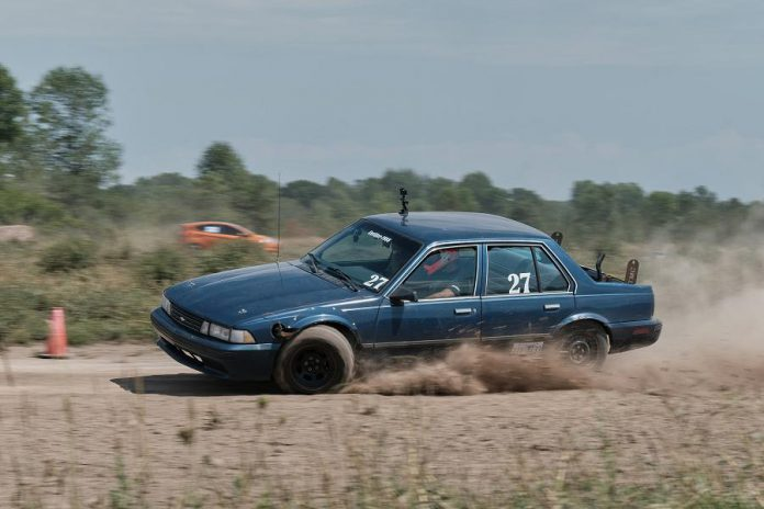kawarthaNOW writer Paul Rellinger's former 1988 Chevrolet Cavalier, modified by Jeremy Kelly, Tyler Junkin, Nate Mitchell, and Andy McCann, on race day at the Free Flow MX Park and Campground near Belleville. (Photo courtesy of Larry and Ben Strung / StrungFoto)