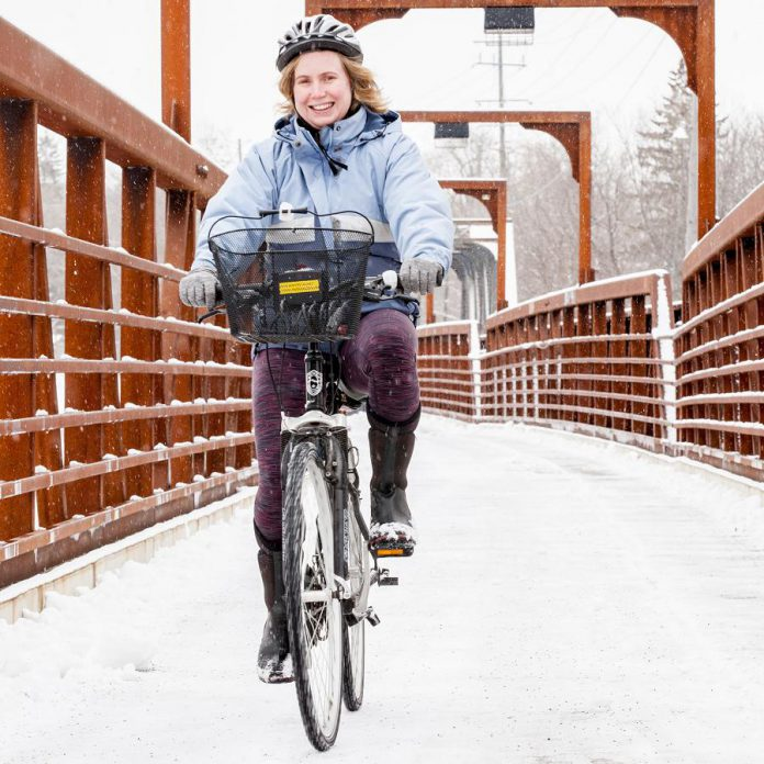 Learning how to manage cold and snowy conditions can extend your personal cycling season. Here, cyclist Jules Sutcliffe is riding over the downtown Peterborough railway bridge in January. (Photo: Vicky Paradisis)