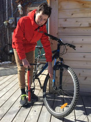 Aaron makes sure his tires are properly inflated; the correct pressure range for a tire is marked on the sidewall. You can get a bike pump with a built-in pressure gauge at local bike shops. (Photo: Jackie Donaldson)
