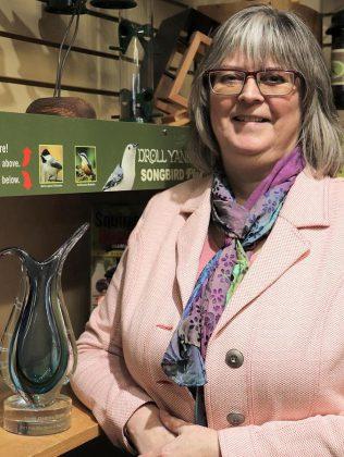 The Avant-Garden Shop owner Brenda Ibey with 2021 Wild Bird Store of the Year Award from Newmarket-based Wild Bird Trading, the leading supplier to the wild bird industry across Canada. During some period during lockdown, trucks of birdseed were literally being delivered to Ibey's store. (Photo courtesy of The Avant-Garden Shop)