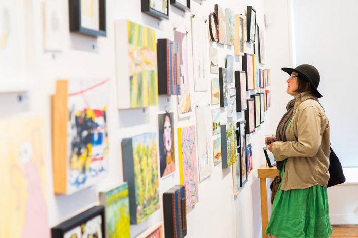 An arts supporter browses works by local artists at the annual Artspace 50/50 auction in 2019. Normally an in-person social event, the 2020 auction was cancelled because of the pandemic but is returning in virtual from April 26 to May 6, 2021 thanks to Melinda Richter, owner of Peterborough art appraisal and auction company Curated. (Photo: Matthew Hayes)