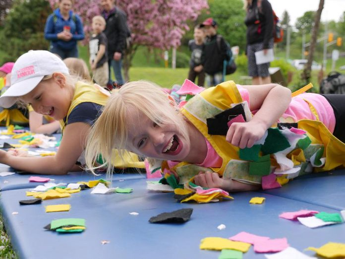 """Normally held at Peterborough's Riverview Park and Zoo, the Peterborough Children's Water Festival is going virtual in 2021 with online fun and educational activities throughout May.  Pictured are kids at the 2018 festival participating in an activity called """"Rolling in the Shed"""", in which they imitate raindrops picking up pollution throughout the watershed. (Photo: GreenUP)"""