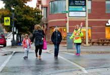 A family crosses Mark Street at Hunter Street in Peterborough's East City, a neighbourhood whose residents have access to almost everything they need within a 15-minute walk, including elementary schools, a grocery store, a drug store, restaurants, playgrounds and parks, public transit, and more. (Photo courtesy of GreenUP)