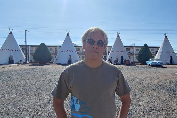 """In """"Going Native"""", host Drew Hayden Taylor examines and breaks down stereotypes of Indigenous peoples. Here he stands in front of The Wigwam Motel, a motel chain in the U.S. built during the 1930s and 1940s. As Taylor points out in an episode, the rooms are actually built in the form of teepees. (Photo courtesy of Ice River Films)"""