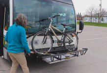 Susan Sauve, transportation demand management planner with the City of Peterborough, demonstrates unloading a bike from a bicycle rack on the front of a Peterborugh Transit bus. The bike racks are part of a pilot program and are available on a limited number of buses on Routes 4, 5, and 8. (YouTube screenshot)