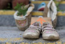A pair of children's shoes on the steps of Peterborough City Hall, part of a community memorial created in response to last week's discovery of the remains of 215 Indigenous children buried at the former Kamloops Indian Residential School in British Columbia. (Photo: Bruce Head / kawarthaNOW)