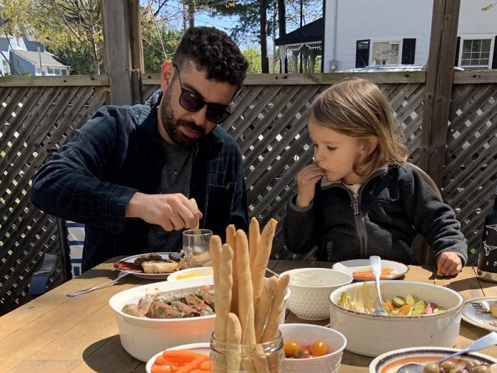Tuncay Alkan enjoying a meal with his family. Cooking Middle Eastern food here in Canada helped him to adjusted to his new country by connecting him back to the land, culture, and family he left behind in Turkey. He also speaks with his family in Turkey on the phone almost every day.  (Photo courtesy of the Alkan family)
