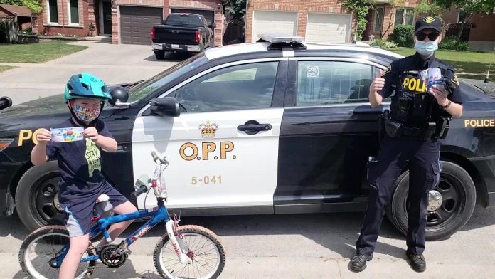 A child with a coupon for a free 'Froster' at a local Circle K convenience store from a local OPP officer. Under the OPP's positive ticketing program, kids will be rewarded this summer for practising personal safety (such as by wearing a bicycle helmet), performing good deeds, and more. (Photo: OPP)