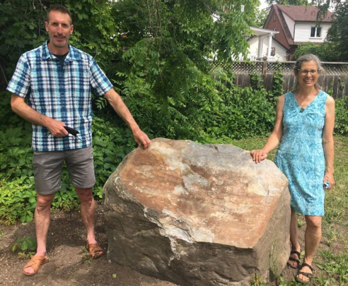 Ashburnham Ale House owner Scott Wood and City of Peterborough transportation demand management planner Sue Sauve stand by the boulder that will soon be home to an embossed metal plaque that will recognize the contributors to the $60,000 cost of lighting the Rotary Greenway Trail from Hunter Street East to Douro Street in Peterborough's East City. (Photo: Paul Rellinger / kawarthaNOW)