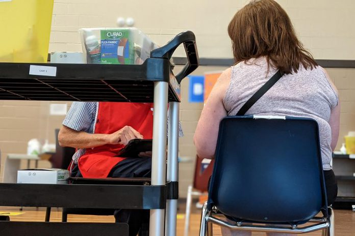 A woman receives her first dose of the Pfizer vaccine at the mass vaccination clinic at the Evinrude Centre in Peterborough on May 26, 2021. (Photo: Bruce Head / kawarthaNOW)