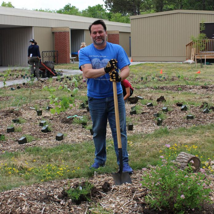 Scott Pepin, CEO of Five Counties Children's Centre, plants trees, shrubs, and perennials in the new Therapy Garden. (Photo: Genevieve Ramage)