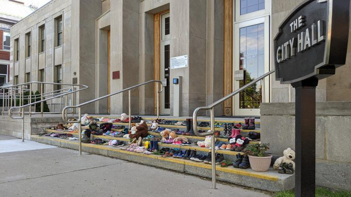 After the remains were discovered of 215 Indigenous children buried at the former Kamloops Indian Residential School in British Columbia in May 2021, the Indigenous community of Nogojiwanong-Peterborough created a memorial on the steps of Peterborough City Hall. On August 3, the 215th day of 2021, members of Curve Lake and Hiawatha First Nations will hold a day of mourning in Nogojiwanong-Peterborough to remember and recognize all Indigenous children whose lives were lost to Canada's residential school system. (Photo: Bruce Head / kawarthaNOW)