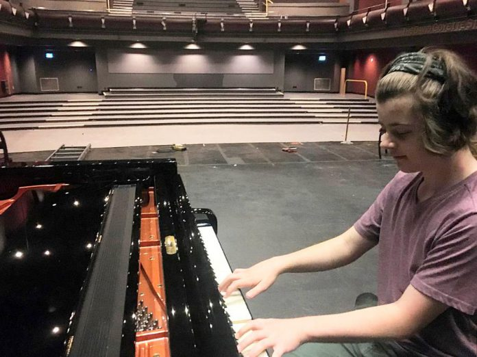 Quinn Vandermey performs on the piano to a temporarily seatless main theatre at Showplace Performance Centre in downtown Peterborough. New state-of-the-art seats will be installed in the Erica Cherney Theatre by October 2021, with the venue planning to welcome audiences into those new seats in November. Supporters of the non-profit organization can help cover the $410,000 cost of the project by purchasing naming rights for the seats. (Photo: Paul Rellinger / kawarthaNOW)