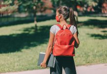 A young masked female student wearing a backpack and carrying books. (Stock photo)
