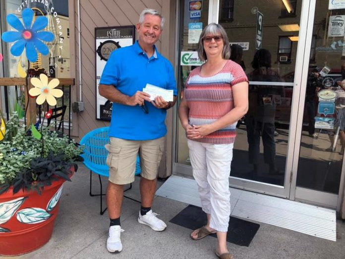Dave McNab accepting the $1,000 donation from Brenda Ibey, owner of The Avant-Garden Shop, on August 5, 2021. (Photo: Clayton Ibey)