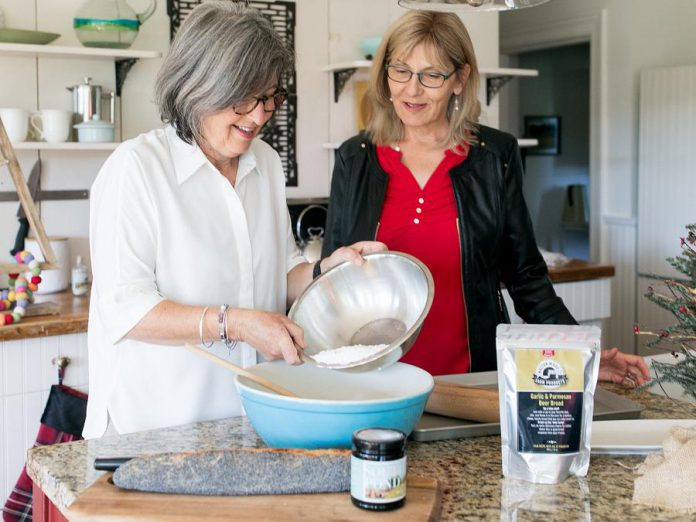 South Pond Farms owner Danielle French in the kitchen with her friend Leslie Scott, owner of Walton Wood Farm. Scott, who primarily sells her brand of personal self-care products as well as some food products (such as the garlic and parmesan beer bread mix pictured) has expanded Walton Wood Farm's product line to include South Pond Farms' gourmet food products, which include jams, marmalade, honey, sauces, baking mixes, and more. (Photo: Ash Nayler Photography)