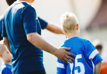 A coach supporting a young player during a soccer game. (Stock photo)