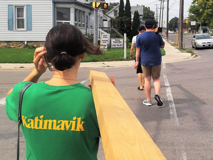 Katimavik volunteers carry lumber and other supplies back to their house in Peterborough where they built a Little Library to provide free access to books in the neighbourhood. Katimavik participants were in six communities across Canada this past summer, including Naniamo, Calgary, Winnipeg, Peterborough, Quebec City, and Moncton, all working to make a difference in the communities they were living in.  (Photo: Georgia MacKinnon)