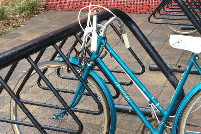This bike may seem like it is locked, but look closely: the lock does not actually go through the frame. For the best security, a lock should secure the frame as well as both of the wheels.  (Photo courtesy of GreenUP)