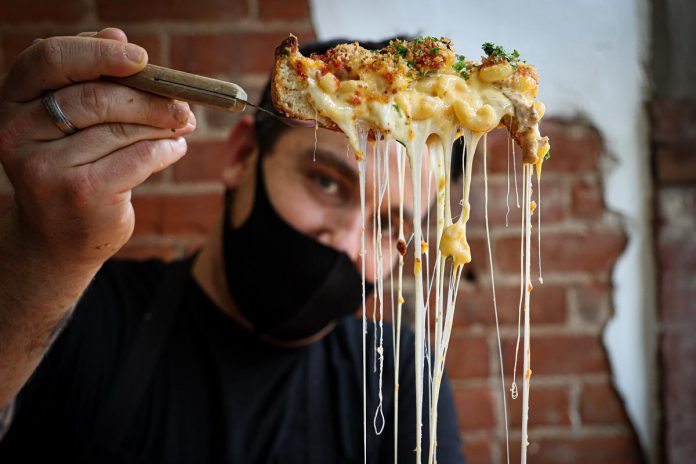 """Taso Hatzianastasiou, owner and chef of Taso's Restaurant and Pizzeria, shows off his Chicago-style deep dish """"Mac n Cheeza"""" with spicy chorizo sausage, porchetta, and jalapeno, topped with three cheeses and a garlic parm crusted panko. (Photo: Mac + Cheese Festival / Peterborough DBIA)"""